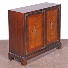 East Asian Style Cabinet: An East Asian cabinet. This cabinet is a western interpretation of an East Asian cabinet, with elm wood veneers on the doors, crossbanded with mahogany, with brass reinforcements and asian style drop pulls, all on hardwood base with square feet. The interior of the doors features counterchanged panels of light and dark mahogany veneer with one shelf inside. Unmarked.