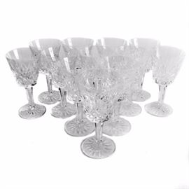 "Waterford Crystal ""Lismore"" Cordial Glasses: A set of twelve Waterford Crystal cordial glasses in the Lismore pattern. Each piece is decorated with vertical cuts to the bowl, multisided stems, and round bases adorned with starburst motifs. They are marked ""Waterford"" to the underside."