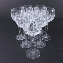 "Waterford Crystal ""Lismore"" Wine Hock Glasses: A set of eight Waterford Crystal Lismore patterned wine hock glasses. Each glass includes vertical cuts on a rounded bowl body with multi-sided stem ending in a wide foot with cut underside. The foot is marked ""Waterford""."
