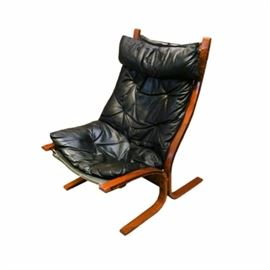 """Siesta"" Style Lounge Chair: A Danish Modern style lounge chair after Ingmar Relling's famous Siesta design. It has a dark stained wooden frame that slopes down the back and bends back to form the back legs, with the seat frame sloping and bending to form the front legs. The back and seat support is a black mesh, tied to the frame. It has a padded head rest pillow, back, and seat, all upholstered in black leather with button tufting accents.  Matching chair in 17DAL209-305."