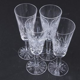 "Waterford Crystal ""Lismore"" Champagne Flutes: A set of four Waterford Crystal champagne flutes in the Lismore pattern. Each flute displays a cut crosshatch and vertical line motif faceted stem and cut starburst design to the foot. Each flute is marked ""Waterford"" to the underside."