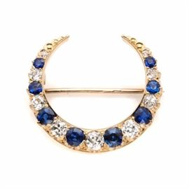 18K Yellow Gold Sapphire and Diamond Crescent Brooch: An 18K yellow gold sapphire and 0.87 ctw diamond brooch with a 10K yellow gold stem. This crescent-shaped brooch features alternating sapphires and diamonds in a graduating pattern.