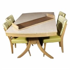 Vintage Mid Century Modern Dining Table and Chairs: A vintage Mid Century Modern dining table and chairs. This table features a rectangular laminate top over a set of four splayed legs. The four chairs feature a vinyl upholstered back over an upholstered seat that rises above splayed and tapered legs.