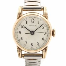 Vintage Gold Filled Hamilton Wristwatch: A vintage gold-filled Hamilton wristwatch. This timepiece features an Arabic and slash numeral face, with black hands and silver-toned second hand. The case is attached to a silver-toned expandable band.