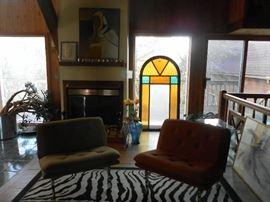 Stained glass window, mid century modern Barcelona style chairs, zebra rug