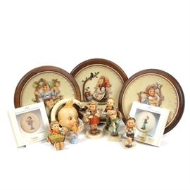 Collection of Hummel Plates and Figurines: A collection of Hummel plates and figurines. Included are three collector plates with raised images of children, which are framed in wood. There is a wall hanger ornament depicting a baby's head within a ring. Two miniature Hummel plates marked with dates of 1984 and 1986. Also included are six Hummel figurines, depicting children and angels. All are marked as Hummel, with a variety of different Hummel maker's marks from different years.