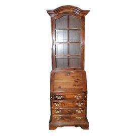 """Pine Chippendale Style Secretary Bookcase by Ethan Allen: A Chippendale style secretary bookcase by Ethan Allen. This stained pine piece has a top and bottom portion which separate. The top has an arched and beveled cornice over a glass paned cabinet door with wooden overlay and gold colored handle. Inside are four wooden shelves with plate lines, and two of the shelves are adjustable. The bottom portion has a secretary with slant front that rests on pull out slats and opens to scalloped and turned column divided storage. The desk sits over four drawers with gold bails and batwing plates; the entire piece is raised on a scalloped apron and corner bracket feet. It comes with a skeleton key for the desk. """"Ethan Allen"""" is marked inside a drawer."""