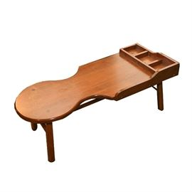 Cherry Cobbler's Style Workbench Coffee Table: A vintage cobbler's style workbench coffee table. This cherry table has a rounded seat with a platform in front with divided compartments, and it rests on straight, square legs.