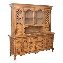 French Provincial Buffet with Cabinet Attributed to Thomasville: A large French Provincial style buffet with cabinet, attributed to Thomasville. The cabinet is made of poplar wood, with a pecan color aged and distressed finish. There is crown molding at the top, with beaded panels down the sides. Two lattice panel cabinets flank an open shelf and two glass front cabinets on the top. The bottom cabinet has an overhung top with rounded corners, above three center dovetailed drawers, flanked by cabinets with recessed and arched panels. The interiors of the cabinets have shelves, and a flatware drawer is fitted with dividers and brown flannel cloth on the bottom. The cabinets and drawers are fitted with brass pulls. A scrolled skirt trims the bottom, and the display cabinet rests on short, curved, cabriole legs. Please note, this very large, very heavy item is located on a main floor, and it comes apart in two sections for easier transport.