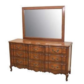 Vintage French Provincial Style Cherry Dresser with Mirror: A vintage French Provincial style cherry dresser with mirror. This piece features a rectangular top dresser with beveled edges and scalloped trim over nine side by side drawers with serpentine facade featuring dovetail joinery and decorative brass handles. This piece sits on cabriole legs joined by a scalloped apron and terminating on whorl feet. Also includes a rectangular mirror with wooden frame featuring egg and dart molding. There are no visible maker's marks.