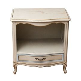 "Drexel French Provincial Bedside Cabinet: A vintage Drexel French Provincial bedside cabinet. The cabinet is made of wood, with a white painted finish, accented with gold painted edges and details. It has a curved front edge on the top, with an open cabinet below. There is a single dovetailed drawer at the bottom, which is accented with a light blue border around the drawer panel, and it has a brass tone metal handle. The cabinet rests on short, cabriole legs, and is marked ""By Drexel""."