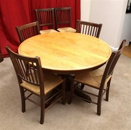 Maple Finished Dining Table and Six Walnut Stained Chairs: A maple finished dining table, having a round top and wide leaf, both having a molded edge and dark stained apron, above a turned pedestal base on four shaped feet with heavy reeding. The six walnut stained side chairs, each have spindled backs, rush woven seats and stretchered legs.