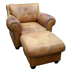 Vintage Leather Chair and Ottoman: A vintage leather chair and ottoman. This set includes a chair with straight crest rail and slant, cushion back with rolled armrests flanking a removable seat cushion. The chair features brass nailhead trim to the front and terminates on wooden feet. Also includes a square, cushion top ottoman terminating on wooden feet. Both pieces feature a light brown leather. There are no visible maker's marks.
