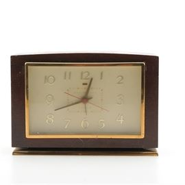 "General Electric Vintage Alarm Clock: A General Electric vintage alarm clock. The clock has a brown rectangular wooden case with a brass bezel. The clock features an off-white face marked ""General Electric Alarm"" with gold tone Arabic numerals and hands and a red second hand. The back has alarm and time set dials and a sticker on the bottom that reads ""General Electric Clock, Model 7H 189"". Time keeping accuracy not guaranteed."