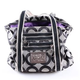 "Coach Poppy Op Art Glam Tote Bag: A Coach Poppy Op Art Glam tote bag. This purse is constructed from a gray and black san-serif signature C jacquard, with two front zip pockets, and black grosgrain straps with silver metallic leather trim. The interior is lined in a purple satin with leather creed patch and serial number ""No. G0969-13826""."