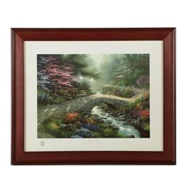 "Reproduction Print After Thomas Kinkade ""Bridge of Faith"": A reproduction print on paper titled Bridge of Faith after listed American artist Thomas Kinkade (1958 – 2012). This work depicts a stone foot bridge over a narrow creek leading through a forest blooming with flowers dappled in sunlight. The piece is signed in plate to the lower right, includes the artist's seal to the lower left margin, and a blind stamp to the lower right margin reading ""World Vision."" It is also titled in an inscription to the lower center margin. The print is presented behind glass in a wooden frame with a hanging wire to the verso."