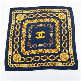 "Chanel Silk Scarf: A Chanel silk scarf. This navy blue and gold tone scarf features a interlacing chain link design. The original decal is present to the scarf reading ""100% Silk Reine Seide All Silk Made in France""."