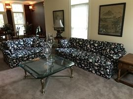 Floral sofa and loveseat, heavy glass and metal coffee table, oriental art