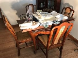 High-end dining room table with 4 chairs that have wicker inserts