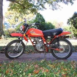 Honda 1977 4-Speed Motorcycle For Restoration: A Honda 1977 4-speed motorcycle for restoration; VIN is XL75-1019599 and mileage is 41700. Currently inoperable. Features include a deep orange color frame with lighter orange accents, and a black leather seat.