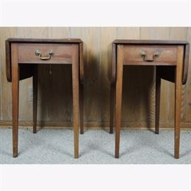 Pair of Pembroke Tables: A pair of Pembroke tables. Made of solids and veneers, these vintage drop-leaf tables feature radius corners, single inset drawers with dovetail joinery, patinated brass bail pull handles, and square tapered legs. They are finished to the back.