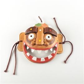 Korean Painted Wood Mask: A Korean painted wood mask. This mask depicts a character with exaggerated features including wide eyes and large red, smiling lips with white jagged teeth. It is complete with braided straps to either side and a metal hook affixed in verso. The mask is marked with a seal on the back that is covered by the hardware.