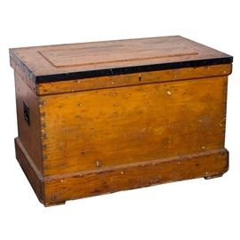 Antique Pine and Curly Maple Tool Chest:An antique dovetailed pine tool chest with curly maple fitted interior, circa mid-19th century. This rectangular piece features a hinged, planked top with raised central panel and banded metal edges. The interior reveals a curly maple planked top with two curly maple sectioned trays with a lower sliding board storage area. The outside of the case has a keyhole in the top trim board above a pine panel front showing hand dove-tailed joined edges. It is mounted to a tray style stand with squat block feet and includes iron handles at each side.
