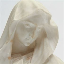 """Italian Marble Bust of the Madonna: An Italian marble bust of the Madonna. This bust, rendered in white marble depicts the Virgin Mary in a draped veil, glancing down. It is presented atop a removable base and is etched with """"15"""" to the bust and base. Etched along the neck of the bust is """"Made in Italy""""."""