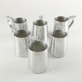 "Mid 20th Century B.W. Buenilum Hammered Aluminium Mugs: A set of mid 20th-century aluminum mugs by B.W. Buenilum. This collection includes six identical mugs with a hammered texture body and a riveted handle with a flared thumb tab. The undersides are stamped, ""B.W. Buenilum"" wit a castle mark."