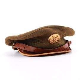 "World War II Army Air Corp Hat: A World War II U.S. Army Air Corp hat. This circa 1944 visor hat features a brown leather visor, a band of olive colored canvas is surrounded by a strip of sizing leather, and is topped with a woolen beret style cap. The cap is embellished with a circular gold toned metal medallion depicting a crest, an eagle with spread wings, and a banner reading ""E Pluribus Unum""."