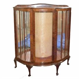 Queen Anne Style Bow Front Display Cabinet: A Queen Anne style bow front display cabinet. This piece features an arched splash over a pair of bowed glass side doors and bowed center panel, rising up on cabriole legs ending in pad feet. The piece includes figured veneers, interior mirrors, and decorative escutcheon.