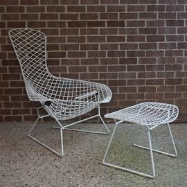 "Harry Bertoia ""Bird"" Style Chair and Ottoman Frames: A chair and ottoman frame after the famous Bird design by Henry Bertoia. The chair has a narrow back that widens significantly to a saucer style seat and arms, made of coated wire and raised on a coated rod frame with sled base. The ottoman is curved to the top and bowed on one end, also made of a coated wire grid and raised on coated rod base. No visible maker's marks."