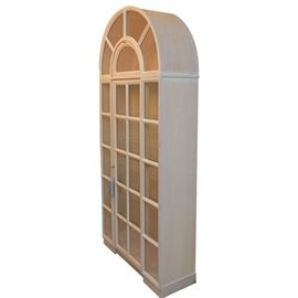 Arched Top Display Cabinet: An arched top display cabinet. This piece features a two-piece unit with arched and rectangular glass panel design including muntins, a drop panel door and a rectangular door. The piece includes interior shelving, has a pickled finish and terminates in wide bracket feet.