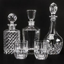 "Crystal Barware Featuring Nachtmann: An assortment of crystal barware. It includes three decanters and two rock tumblers. Two decanters are decorated with pressed designs including cross-hatch and diagonal designs. The decanter that is simplistic in design is etched ""Nachtmann"" to the underside. The tumblers feature simplistic linear designs and have no visible maker's marks."