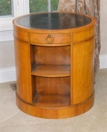 "Baker Furniture Bookcase Round Drum Side Table: A round wood bookcase drum table by Baker Furniture. With a black leather inlay with embossed leaf edge, this table features three sections of two shelves separated by medallion side panels, with one center drawer. The wood is thought to be fruitwood. The drawer is marked ""Baker Furniture."""