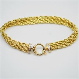 14K Yellow Gold Diamond Bracelet: A 14K yellow gold diamond bracelet. This multiple strand woven link bracelet features diamonds stations on either side of the round closure.
