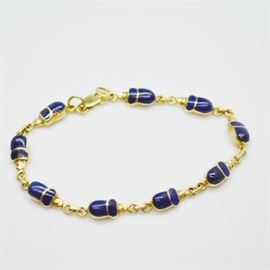 18K Yellow Gold Lapis Lazuli Bracelet: An 18K yellow gold lapis lazuli bracelet. The gold links feature a lapis lazuli inlay design, separated by rolo chain links.