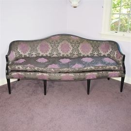 Upholstered Camelback Sofa: A vintage upholstered camelback sofa. Upholstered in a metallic taupe fabric, it features a lilac medallion design amid a gray damask type vining floral, with charcoal welting. It features a dark charcoal painted wood frame, tapered legs, and a removable feather filled seat cushion with a zippered cover. Unmarked.
