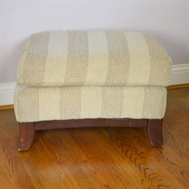 Oatmeal Striped Ottoman: An vintage oatmeal upholstered ottoman. This rectangular ottoman features a striped oatmeal and brown striped fabric with a cushion top design, and lower brown stained wood frame. Unmarked.