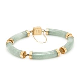 14K Yellow Gold Jadeite Bracelet: A 14K yellow gold jadeite bracelet. This bracelet features five linked carved bar jadeite stones affixed to a box tab clasp embossed with a Chinese character.