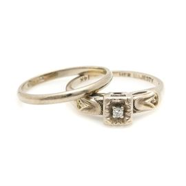 10K and 14K White Gold Bridal Set: A 10K and 14K white gold bridal set. This set includes a 10K white gold band, as well as a 14K white gold engagement ring. The ring showcases a diamond set to a square crown with an etched floral motif. The shoulders of the engagement ring feature etching and milgrain detail.