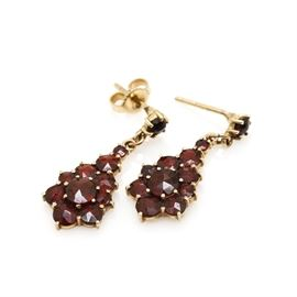 14K Yellow Gold Garnet Dangle Earrings: A pair of 14K yellow gold garnet dangle earrings. Each earring features a cluster of garnets suspended from a garnet set stud.
