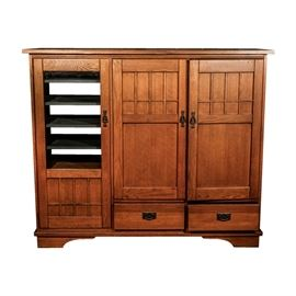 """Mission Style Entertainment Center Cabinet by Hooker Furniture Co.: A Mission style entertainment center cabinet by Hooker Furniture Co. This piece features a rectangular top over a glass panel and two recessed panel doors with decorative pulls, and a pair of drawers with drop bail pulls. The cabinets open to reveal interior component, disc and television storage, and the unit terminates in bracket feet. The piece is finished in an oak veneer. An included pamphlet marks the piece """"Hooker Furniture Corporation""""."""