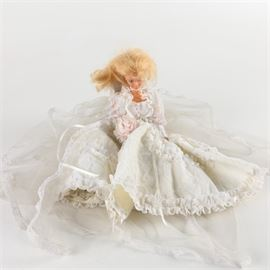 Vintage Barbie in Wedding Gown: A vintage Barbie in a wedding gown. The doll features rooted blonde hair, bright blue eyes, and bubblegum pink lips. She wears a long veil with a lace hem, a voluminous white wedding gown embellished with lace, pearls, and ribbons, and bears a pink bouquet in one hand.