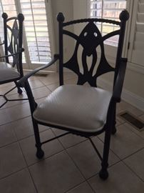 Six heavy iron chairs with fish design on backs, leather cushions, and wheels on the legs.