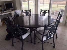 "Custom 59"" Granite Table. There are 6 leather seated chairs. The chairs are iron, fish iron design on backs. Chairs also on wheels. Very, very beautiful."