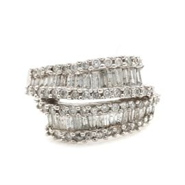 14K White Gold 1.25 CTW Diamond Ring: A 14K white gold 1.25 ctw diamond ring. This ring features baguette diamonds set between rows of round brilliant cut diamonds on a bypass band.