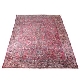 Large Antique Hand-Knotted Persian Sarouk Area Rug: A large antique Persian Sarouk area rug. This wool rug is hand-knotted in a palette of cherry, azure, cream, midnight blue, and pink. It features a classic Sarouk design beginning with a quatrefoil, elaborate floral medallion in the center of a cherry-colored field. The field is densely populated with crisply rendered sprays of flowers, vases, mixed floral bouquets, palmettes, floral fans, and scrolling lancet leaves. Framing the field are six borders, including a densely floral herati main border over midnight blue, two herati minor borders over cream, and two meandering floral minor borders over azure. Selvedges are overcast, the rug finishing at each end with ivory wool warp fringe. Blue weft threads are visible on the underside. The rug is unlabeled.