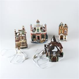 "Christmas Village featuring Department 56: A collection of Christmas village pieces featuring Department 56. There are four buildings included that are composed of porcelain in a variety of styles and color palettes. Included markings are ""Department 56"", ""Dickens' Village Series, The Olde Camden Town Church"" and ""Scrooge & Marley Counting House""."