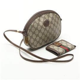 Gucci Coated Canvas Crossbody Bag with Wallet: A Gucci monogram crossbody bag. This designer bag comprises a signature print coated canvas body and brown leather accents including a strap, trim and a logo to the front. The bag has a zipper closure which opens to a tan leather lined interior with a small zippered interior pocket. A gold tone Gucci nameplate and charm zipper pull are present to the interior. The serial number is 007-89-1113. Also included, a Gucci wallet in the signature monogram canvas in brown and tan, with a red and green striped accent. The wallet features a snap closure and currency and credit card pockets. The wallet closes with a gold tone logo snap.